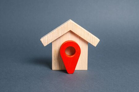 Figurine wooden house and red location pointer. The concept of the location of a building, surrounding infrastructure and the creation of a route to arrive. Moving to another house. Search for options