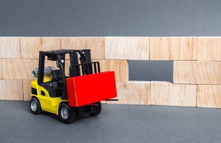 A forklift carries a red block to insert into a wall void. A key element to complete the project, part of the whole. Innovation, concept of idea. Cooperation and collaboration. Teamwork 版權商用圖片