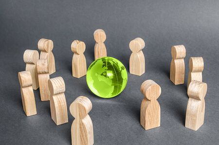 People surrounded a glass globe. cooperation and collaboration of people around the world. Outsourcing and joint work on projects. Diplomacy. crowdfunding. Preserving environment, caring for nature