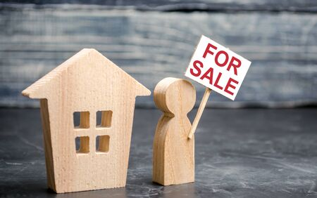 House and person with a sign for sale. Sale of real estate by the owner. Attracting customer attention. Mediation and assistance in buying and selling houses. Search for best housing options on market 版權商用圖片