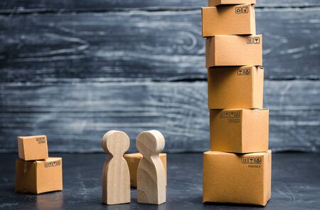 People talk near the tower of cardboard boxes. Services transportation delivery of goods. Online shopping. Concept of business deal, sale of goods. Commerce, retail and distribution. 版權商用圖片