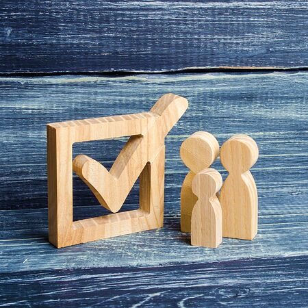 Family figures stand together next to a tick in the box. The concept of elections and social technologies. Volunteers, parties, candidates, constituency electorates. Human rights