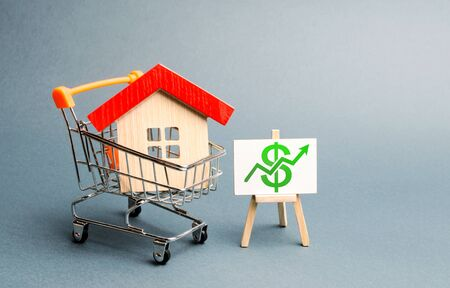 A red roof house in a trading cart and green arrow up on a stand. Increasing the cost and liquidity of real estate. Attractive investing. rising prices or renting. The boom in the property market 免版税图像