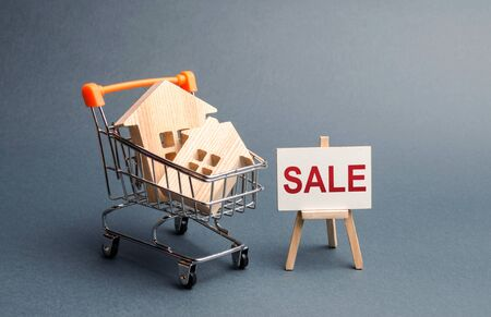 Two houses in a shopping cart and a stand with the inscription sale. selling a home. Announcement of the sale and attracting potential buyers. Advertising campaign. purchase of real estate.