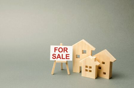 Three houses and a stand with the inscription FOR SALE. Advertising campaign. purchase of real estate. Announcement of the sale and attracting buyers. Construction and sale of housing and offices.