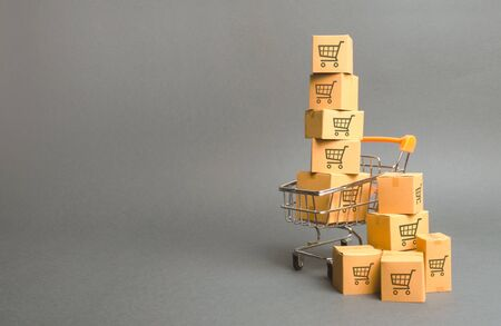 Shopping cart and boxes with drawing of smaller carts. goods sale. commerce, online shopping. Purchasing power, delivery order. E-commerce, sales and sale of goods through online trading platforms. 版權商用圖片
