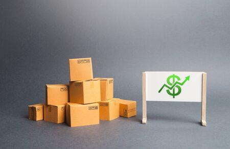 Un mucchio di scatole di cartone e lavagna con il simbolo del dollaro e freccia verde verso l'alto. Il tasso di crescita della produzione. Aumento della domanda dei consumatori. Crescita del reddito dalla vendita di beni. Aumento di prezzo.