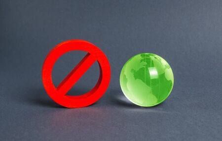 Red prohibition symbol NO and green globe planet earth glass ball. Prohibitions, obstacles and censorship, opponents of globalization and isolationism. Environmental protection, moratorium. 스톡 콘텐츠