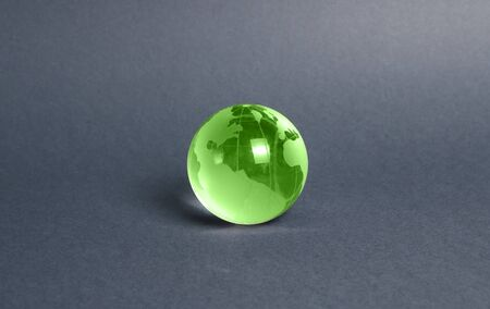 Green glass planet globe on a gray background. International diplomacy. Foreign languages. Globalization and markets. Preservation of the environment and reduction of harmful effects on the ecosystem.