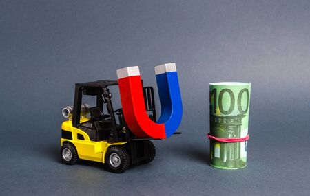 A forklift carries a magnet to a bundle of Euro. Attracting money and investments for business purposes and startups. Increase profits and attract new customers. bonus, cashback. Business strategy. Banco de Imagens - 128846706
