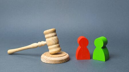 Two figures of people opponents stand near the judge's gavel. The judicial system. Conflict resolution in court, claimant and respondent. Court case, resolution and disputes settling disputes.