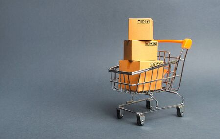A pile of cardboard boxes in a supermarket trolley. concept of shopping in the online store . E-commerce, sales and sale of goods through online trading platforms. Consumer society. Purchasing power
