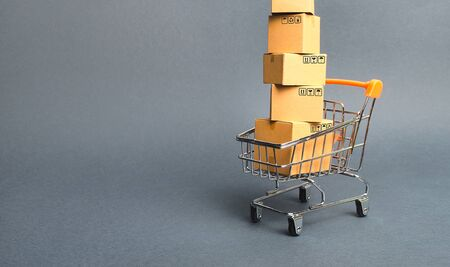 High tower of cardboard boxes on a supermarket trolley. concept of shopping in store. E-commerce, sales and sale of goods through online trading platforms. Consumer society. Purchasing power