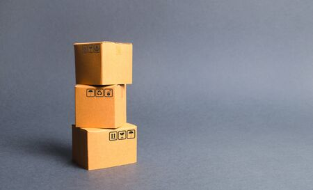 A bunch of three cardboard boxes. The concept of products and goods, commerce and retail. E-commerce, sales and sale of goods through online trading platform. Import and export of products