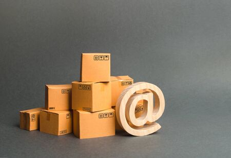 Pile of cardboard boxes and symbol email. shopping. E-commerce. sales of goods and services through online trading platforms. development of Internet network trade, advertising. Retail products Banco de Imagens