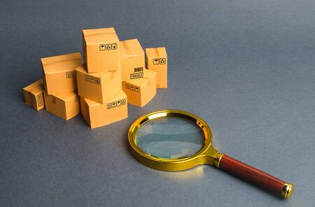 A pile of boxes and a magnifying glass. Concept search for goods and services. Tracking parcels via the Internet. Quality control. Searching for customers, sales and retail. Register of tenders