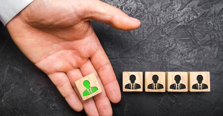 A hand holds out a green leader figure to a team of employees. Headhunter recruits staff and business personnel management. The concept of finding Specialists and workers on the job.