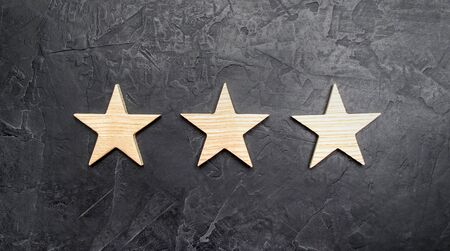 Three stars on a dark background. The concept of rating and evaluation of hotels, restaurants, mobile applications. Excellent quality, buyer choice. Good reviews and impeccable reputation.