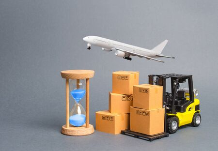 Yellow Forklift truck with cardboard boxesa airmail plane and a sand hourglass. Express delivery concept. Optimization of logistics, improving efficiency. Temporary storage, limited offer Distribution Banco de Imagens