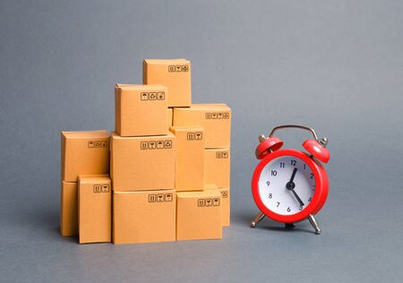 Lots of cardboard boxes and a red alarm clock. Express delivery concept. Optimization of logistics and delivery, improving transportation efficiency. Temporary storage, limited offer and discount.