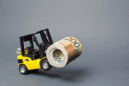 A yellow loader stands on the rear wheels holding a big roll bundle of Euro. concept of attracting investment, issuing concessional loans for business development. High profitability of stock bonds