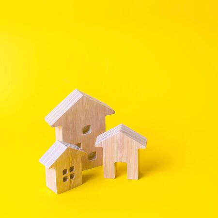 Three houses on a yellow background. Buying and selling of real estate, construction. Apartments and residential buildings in a city or settlement. Investments. mortgage loan. Housing Maintenance Banco de Imagens