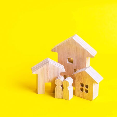 Three houses and people on a yellow background. Buying and selling of real estate, construction. Apartments and residential buildings in a city or settlement. Investments. mortgage loan. Banco de Imagens