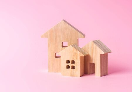 Three houses on a pink background. Buying and selling of real estate, construction. Apartments and residential buildings in a city or settlement. Investments. mortgage loan. Housing Maintenance