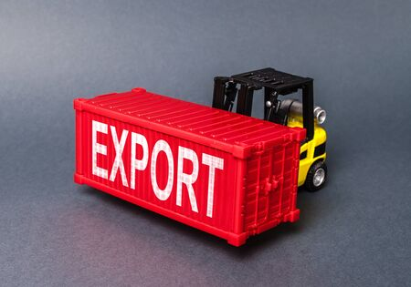 A forklift carries a red freight container labeled Export. concept transportation of goods and products, delivery, shipping. Industry and production, trade balance and distribution. Globalization Banco de Imagens