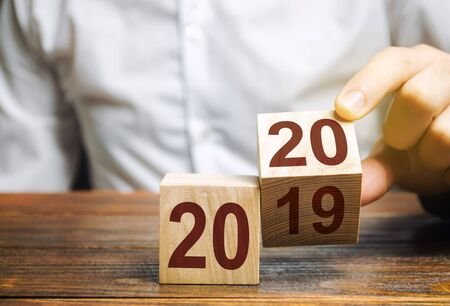 Two wooden blocks with numbers 2019 and 2020. The concept of the beginning of the new year. New objectives. Next decade. Trends and changes in the world. Build plans and goals. Time report