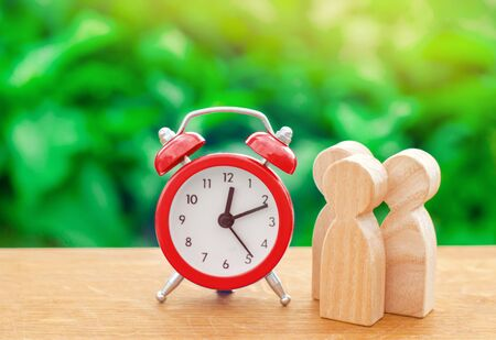 Three wooden human figures standing next to a red alarm clock on a nature background. Time concept. Business, Hourly payment. Man hours. Planning. minimalism