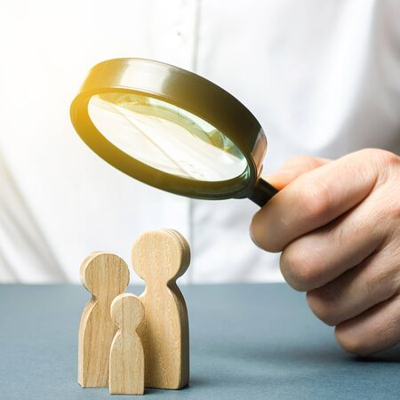 A man looks through a magnifying glass at a family figure. The study of family composition and demographic situation. Statistical data. The program of support for young families, financial assistance.