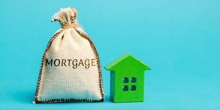 Money bag with the word Mortgage and wooden house. The accumulation of money to pay interest rates on mortgages. Buying a property in debt. Take credit for housing. Loan for home. Real estate