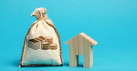 Money bag and wooden house. Concept of real estate market budget. Investment in construction. Saving money to buy a home or apartment. Affordable housing. Mortgage and loan. Taxes. Debt repayment Banco de Imagens