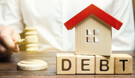 Wooden blocks with the word Debt and a miniature house with a judges hammer. Confiscation of property for failure to pay the debt. The withdrawal of housing. Moratorium. Criminal penalty Banco de Imagens