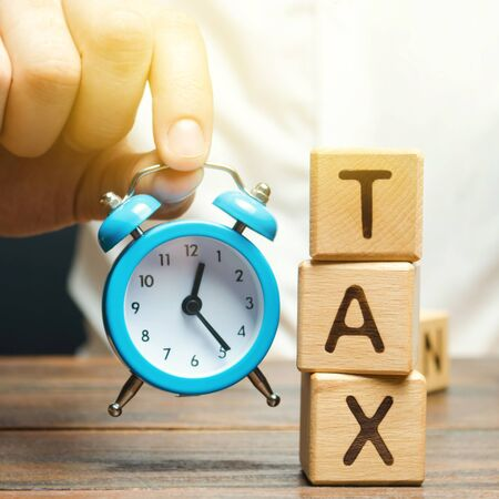 Businessmans hand holding a clock near the wooden blocks with the word Tax. Time to pay taxes. The concept of annual taxation. Taxes on vehicles, property, purchases, luxury. State fee