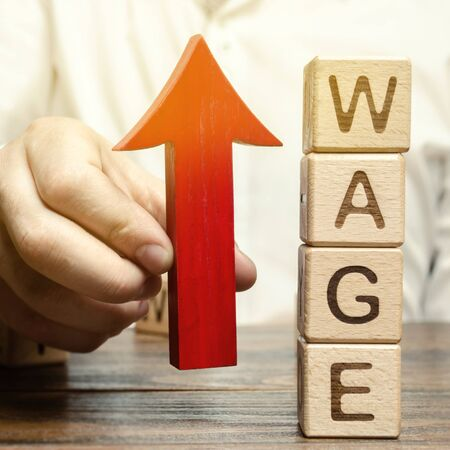 Businessmans hand holds red arrow up near wooden blocks with word Wage. Salary increase concept. Wages rate. Revenue growth and profits. Successful business. Career rise. Promote. Stability