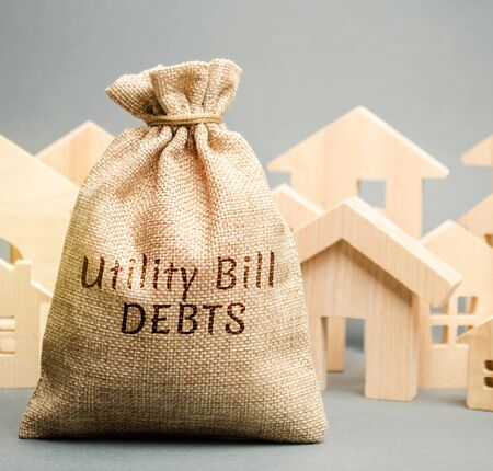 Money bag with the words Utility bill debts and wooden houses. Fines and penalties for failure to pay the debt for electricity and gas. Register of debtors. Stopping the provision of utilities. Banco de Imagens