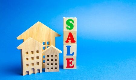 Wooden blocks with the word Sale and wooden miniature houses. The concept of the sell of real estate, apartments and residential premises. Rent and mortgage. Market analysis