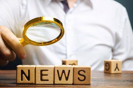 Un giornalista tiene una lente di ingrandimento sopra la parola News. Esamina i principali eventi e analisi. Notizie false. Informazione. Gli eventi più importanti nel Paese e nel mondo Archivio Fotografico