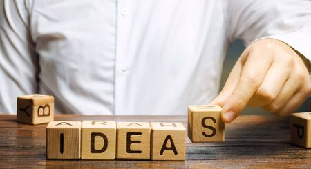 Wooden blocks with the word Ideas and businessman. Generation of innovative business ideas. Creative process. Business strategy and startup. Plan. Planning