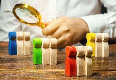Groupes de personnes en bois multicolores et homme d'affaires. Le concept de segmentation du marché. Public cible, service client. Groupe de marché d'acheteurs. Gestion de la relation client. Mise au point sélective