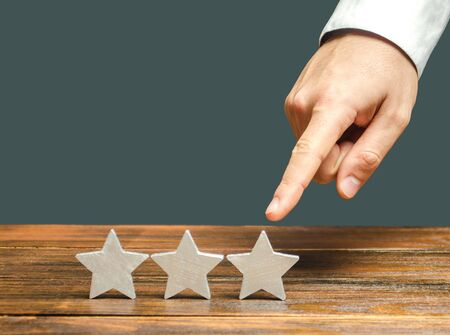 Critic points to third star. The concept of the rating of hotels and restaurants. The evaluation of visitors. Quality level, good service. Customer rating. Feedback.