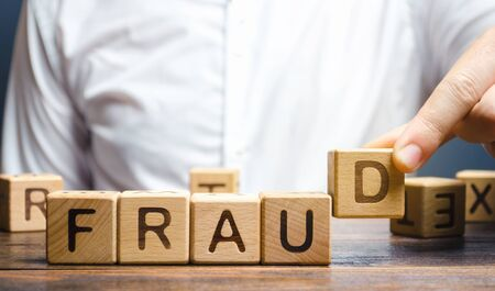 Wooden blocks with the word Fraud and man. Cheating white-collar . The crime. Theft of anothers property. Anti-corruption in the financial sector. Deception and abuse of trust.