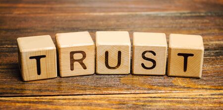 Wooden blocks with the word Trust. Trust relationships between business partners, friends, relatives. Respect and authority. Confidence in a person. Reliable partner Banco de Imagens