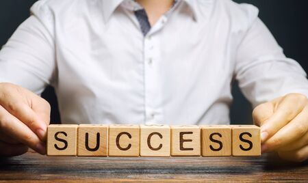 Wooden blocks with the word Success and businessman. Successful business concept. Achieving the goal, overcoming difficulties. The growth of profits and earnings in the company. Performance