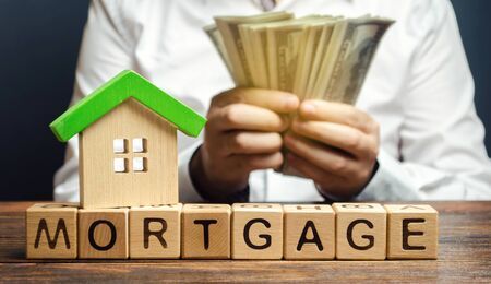 Wooden blocks with the word Mortgage and money in the hands of a businessman. The concept of buying a home on credit. Loan for apartments and housing. Interest rates. Creditor, debtor. Real estate