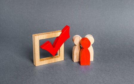 People figurines stand near the checkbox for voting in democratic elections. Lobbying interests, voter bribery, and rigging presidency or parliamentary election results. expression of will Stock Photo
