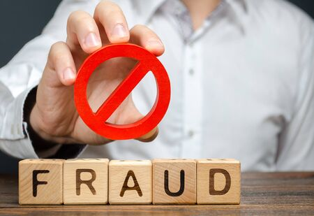 A man holds a red NO prohibition symbol over word fraud. Countering deception, protection against fraudsters. The fight corruption, financial pyramids and business scams. War on crime. Cheaters