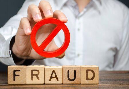 Un hombre sostiene un símbolo rojo NO prohibición sobre fraude de palabras. Lucha contra el engaño, protección contra estafadores. La lucha contra la corrupción, las pirámides financieras y las estafas comerciales. Guerra contra el crimen. Tramposos
